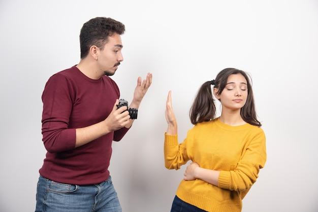 Joli couple avec caméra posant sur un mur blanc.