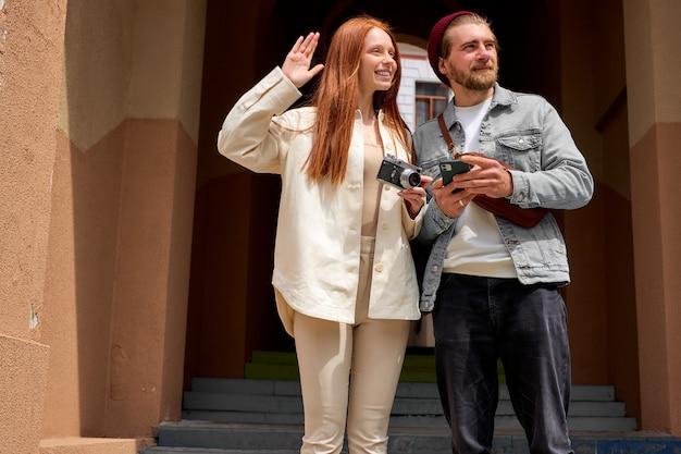Joli couple caucasien prenant des photos avec un appareil photo argentique rétro en marchant.