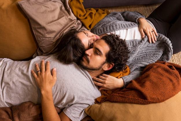 Joli couple couché ensemble sur le canapé