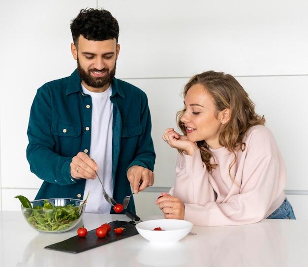Joli couple cuisinant ensemble à la maison