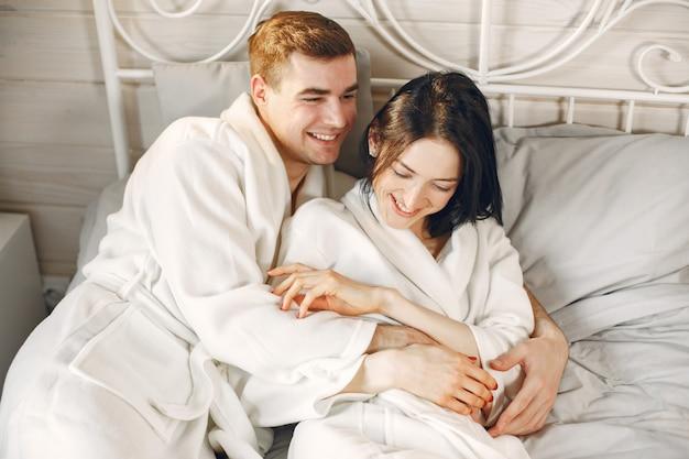 Joli couple dans la chambre portant des peignoirs prenant le petit déjeuner.