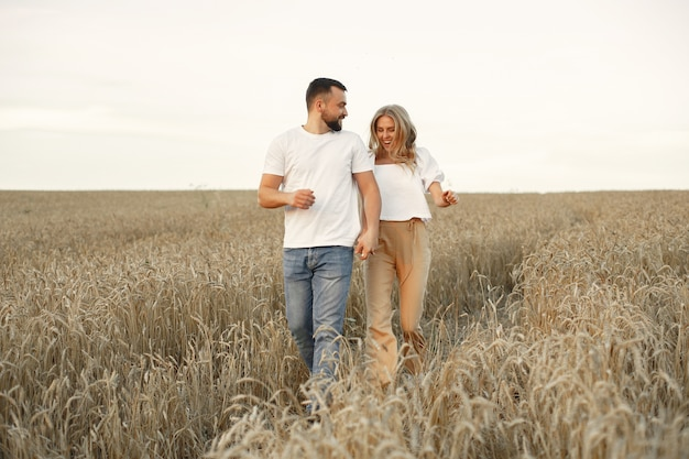 Joli couple dans un champ. dame dans un chemisier blanc. guy en chemise blanche