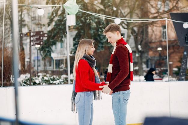 Joli couple dans un chandails rouges s'amuser dans une patinoire