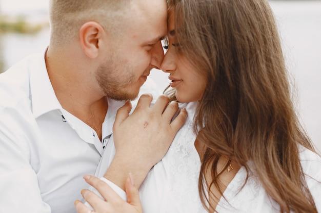 Joli couple dans un parc. dame en chemise blanche. les gens sur la jetée.
