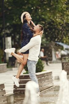 Joli couple dans une ville. homme en chemise blanche. les gens marchent.