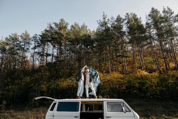 Joli couple debout sur une camionnette à l'extérieur