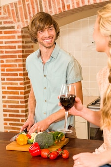 Joli couple en dégustant un verre de vin et de couper des légumes dans la cuisine