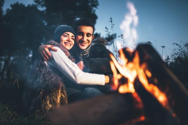 Joli couple de détente près de feu de joie dans la forêt au moment de la soirée