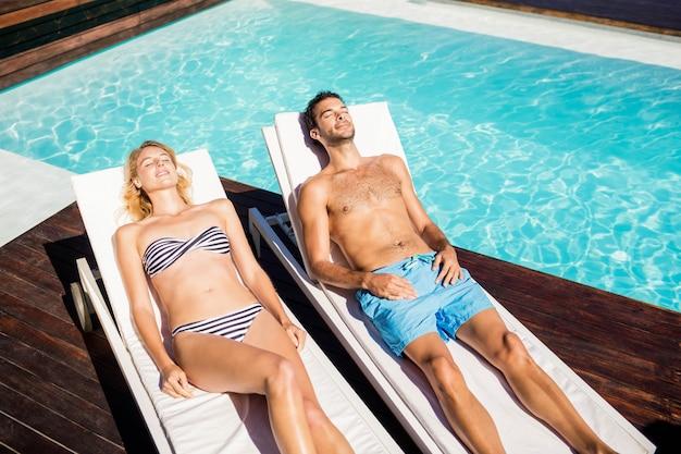 Joli couple de détente sur les transats au bord de la piscine