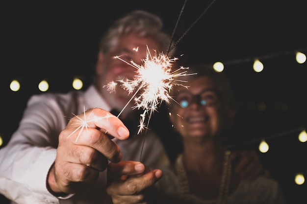 Joli couple de deux personnes âgées amoureuses ensemble la nuit du nouvel an jouant avec les cierges magiques à la main près de la caméra
