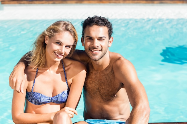 Joli couple embrassant au bord de la piscine