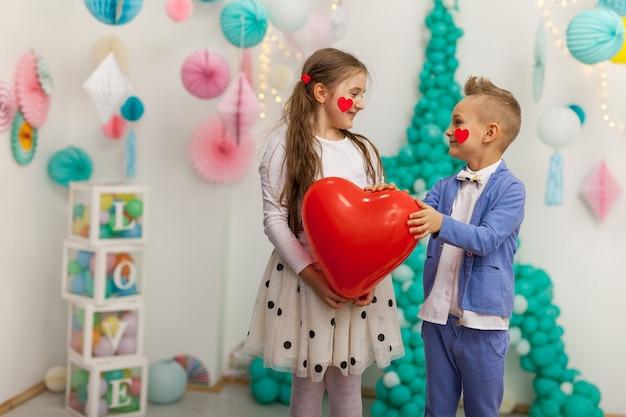 Joli couple d'enfants avec ballon coeur rouge. concept de la saint-valentin et de l'amour, tourné en studio