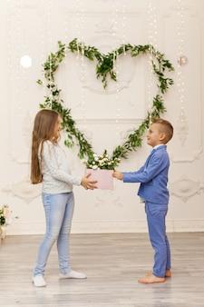 Joli couple d'enfants avec cadeau. concept de la saint-valentin et de l'amour, tourné en studio