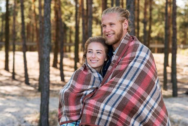 Joli couple enveloppé dans une vue de côté de couverture