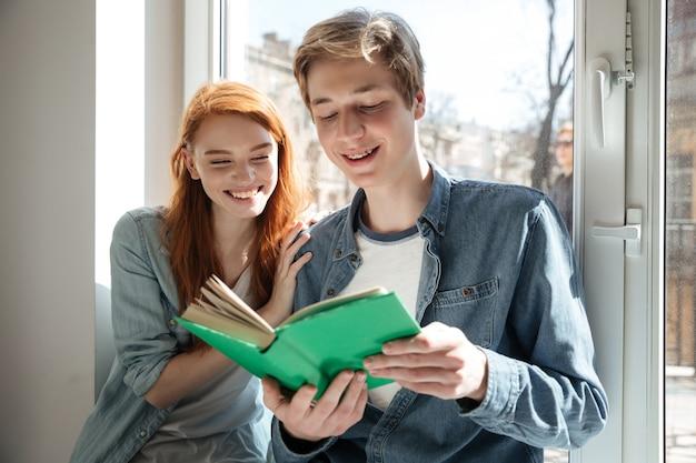 Joli couple d'étudiants lisant un livre