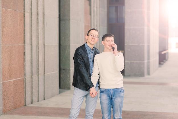 Joli couple gay dans la ville, tendres baisers doux, souriant