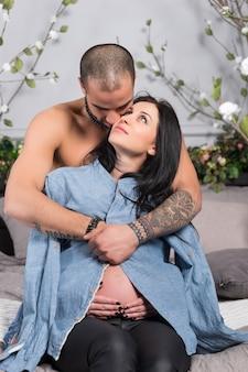 Joli couple international d'homme à la poitrine nue serrant sa femme enceinte brune assise sur un lit douillet gris dans la chambre