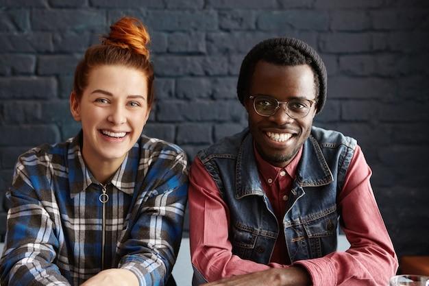 Joli couple interracial se détendre à l'intérieur, assis contre le mur de briques noires
