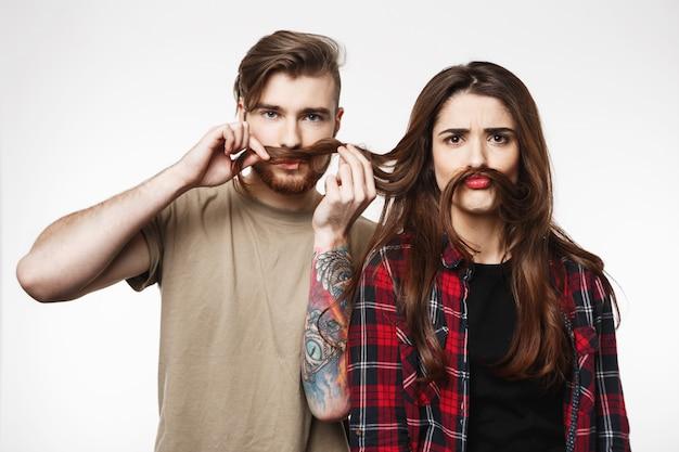Joli couple jouant avec les cheveux, faisant des grimaces idiotes, s'amusant.