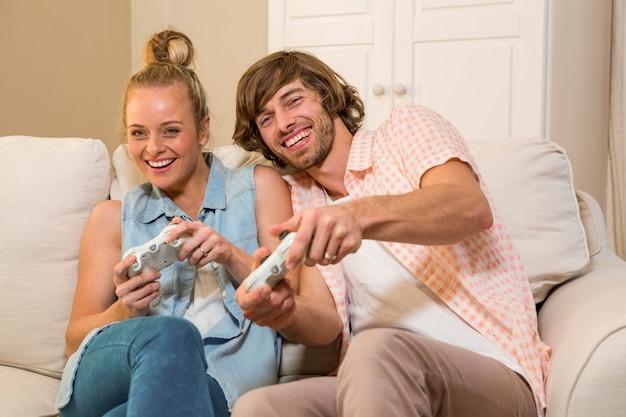 Joli couple jouant à des jeux vidéo assis sur le canapé dans le salon