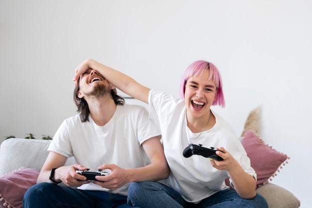 Joli couple jouant à des jeux vidéo sur le canapé
