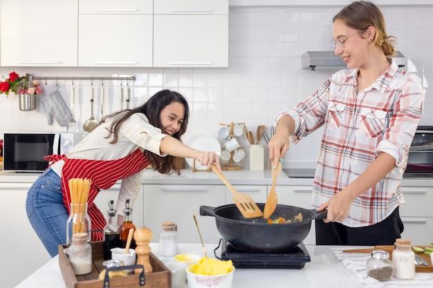 Joli couple joyeux cuisinant ensemble et ajoutant des épices au repas