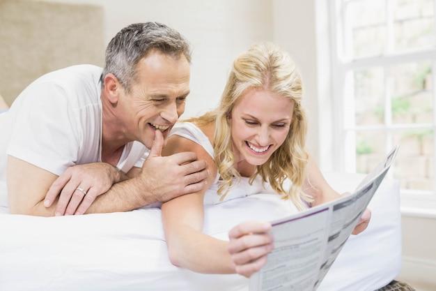 Joli couple lisant l'actualité au lit
