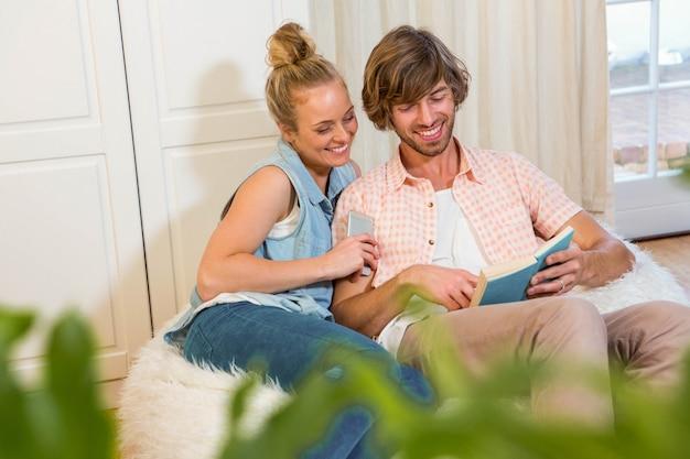 Joli couple lisant un livre et utilisant un smartphone dans le salon