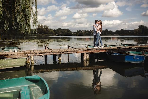 Joli couple marchant près de l'eau. fille dans une chemise blanche. paire au bord de la rivière. aimer le jeune couple près de la rivière avec des bateaux. l'amour sans frontières. mise au point sélective