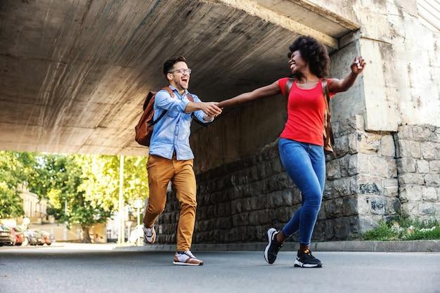 Joli couple multiculturel heureux en cours d'exécution dans la rue.