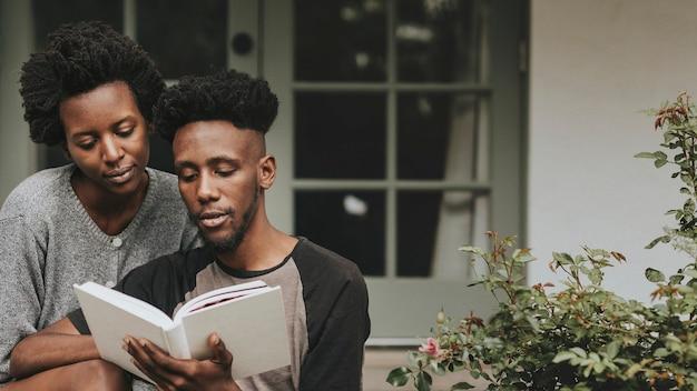 Joli couple noir lisant un livre ensemble dans un jardin