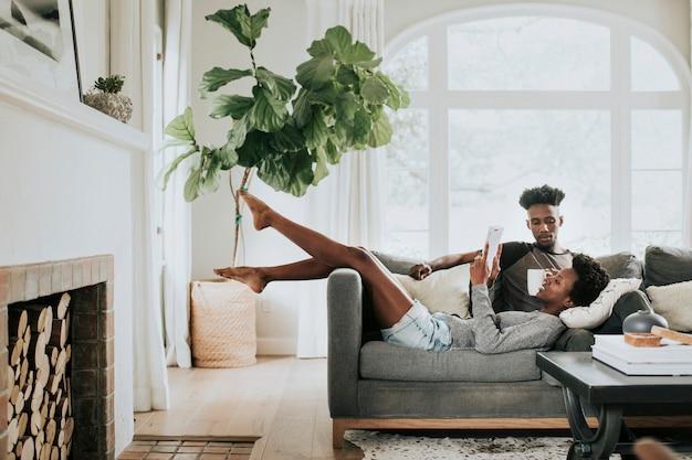 Joli couple noir romantique lisant un livre sur le canapé