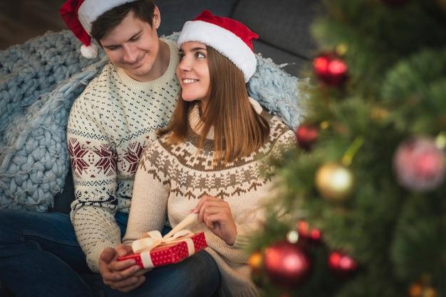 Joli couple ouvrant un cadeau de noël
