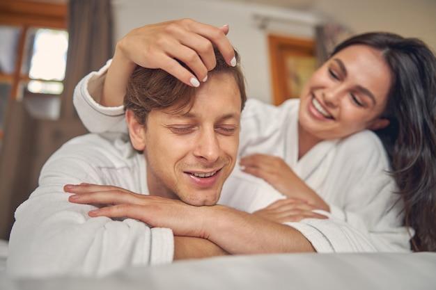 Joli couple en peignoirs blancs se détendre ensemble dans la chambre