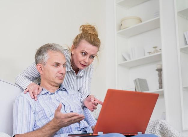 Joli couple de personnes âgées sur un canapé avec ordinateur portable