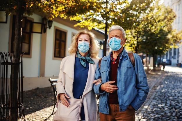 Joli couple de personnes âgées avec des masques de protection sur la marche ensemble dans une vieille partie de la ville.