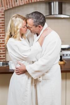 Joli couple sur le point d'embrasser dans des peignoirs dans la cuisine