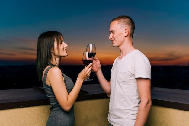 Joli couple portant un verre de vin sur le toit