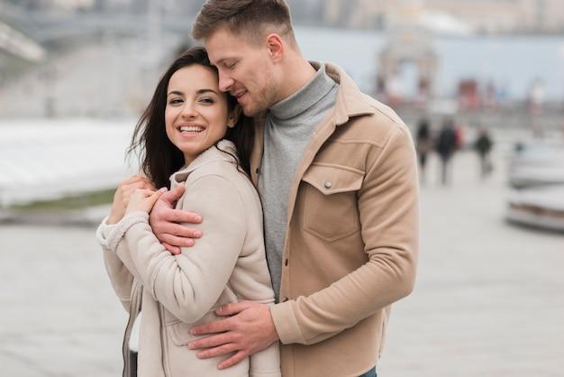 Joli couple posant à l'extérieur
