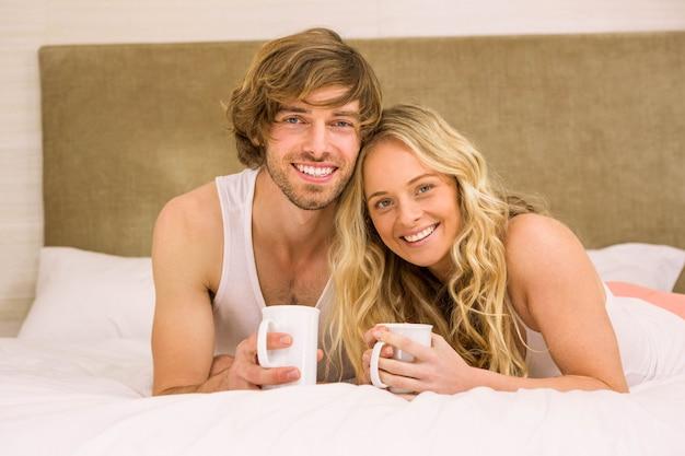 Joli couple prenant un café dans leur lit dans la chambre