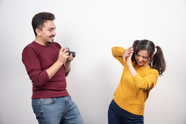 Joli couple prenant des photos avec appareil photo et posant sur un mur blanc.