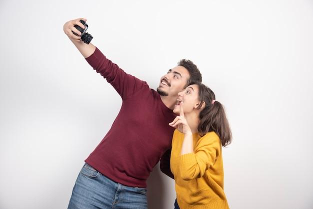 Joli couple prenant selfie avec caméra et posant sur un mur blanc.