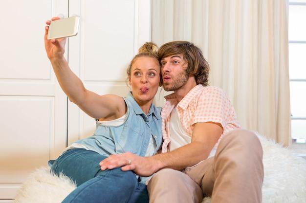 Joli couple prenant un selfie avec smartphone dans le salon