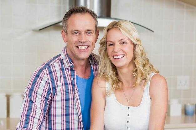 Joli couple regardant la caméra dans la cuisine