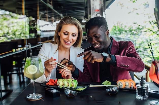 Joli couple s'amusant en mangeant des rouleaux de sushi au restaurant sur une terrasse moderne.