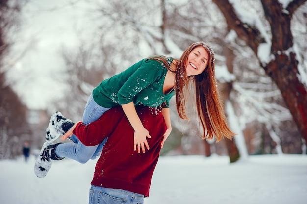 Joli couple s'amuser dans un parc d'hiver