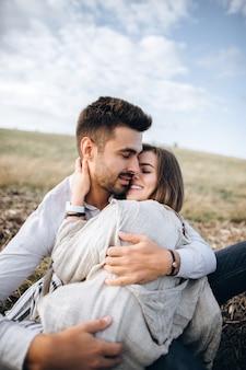 Joli couple s'embrassant, s'embrassant et souriant contre le ciel assis sur l'herbe. espace pour le texte