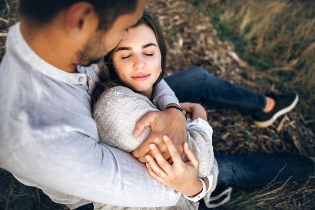 Joli couple s'embrassant, s'embrassant et souriant contre le ciel assis sur l'herbe. portrait en gros plan