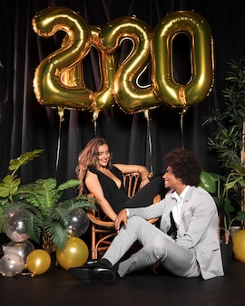Joli couple se regardant entouré de ballons avec le nouvel an 2020