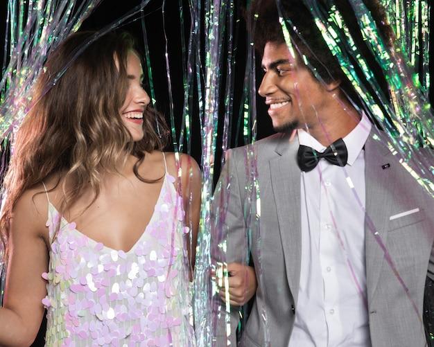 Joli couple se regardant d'un rideau d'étincelles